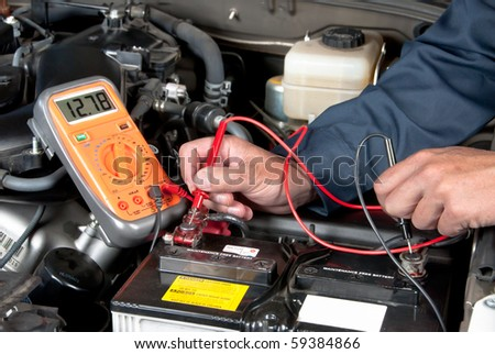 An auto mechanic uses a multimeter voltmeter to check the voltage level in a car battery. - stock photo