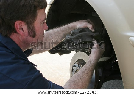 An auto mechanic working on disc brakes,  inserting new brake pads in the caliper. - stock photo