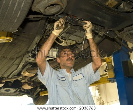 an auto mechanic works on a automobile from underneath