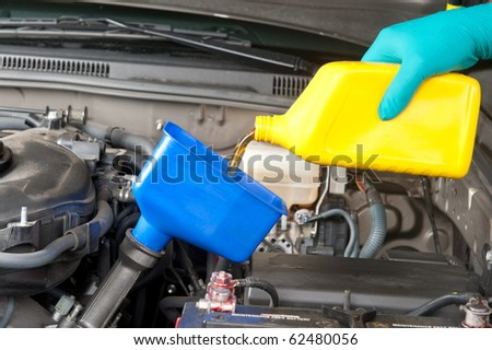 An automotive mechanic changes the oil in a modern car.