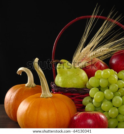 An autumn basket with apple, pear, grapes, wheat and pumpkins (Selective Focus, Focus on apple, grapes and pumpkin in front) - stock photo