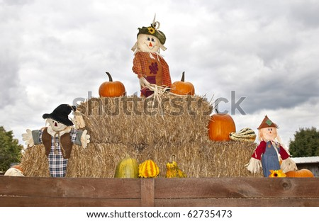 An Autumn display with scarecrows, bails of hay and pumpkins, copy space - stock photo