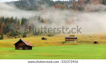 An autumn view of grass field in morning fog with wooden barns by the hillside near Garmisch Partenkirchen and Mittenwald, in Bavaria, Germany