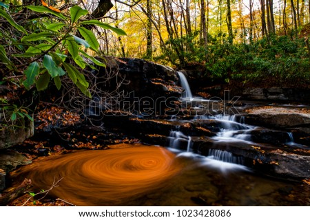 An autumn view with leaves swirling in a circular pattern at Fletcher Run Falls in Ohiopyle State Park in the hills of southwest Pennsylvania.