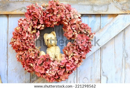 An autumn wreath of faded hydrangea flowers  hanging on a blue, rough painted wooden barn door, a rustic, shabby chic image - stock photo