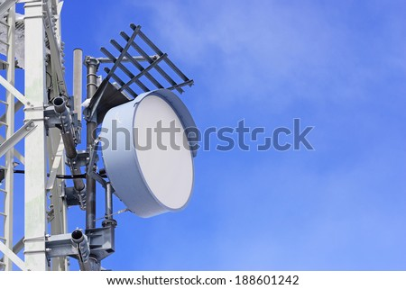 An Close image of a telecommunications dish on a tower against a blue sky