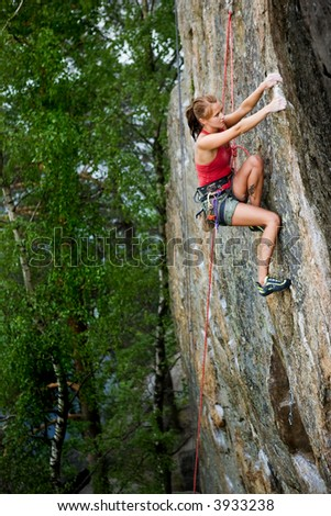 An eager female climber on a steep rock face looks for the next hold. Shallow depth of field is used to isolated the climber with the focus on the head. - stock photo