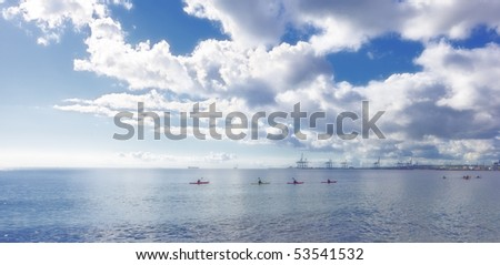 An early morning photo of young people kayaking on the ocean - stock photo