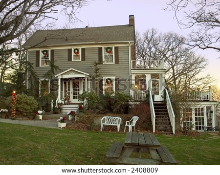 An early morning view of a colonial homed decorated nicely for the holidays. - stock photo