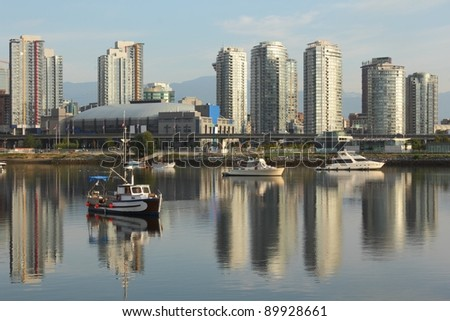 An early morning view of downtown Vancouver's skyline reflected in the still waters of False Creek. Included is the NHL hockey arena and concert stadium. British Columbia, Canada. - stock photo