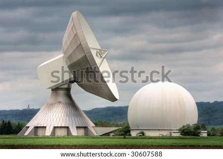 An earth station satellite installation with ancillary building - the type used for broadcasting. Poor weather. - stock photo