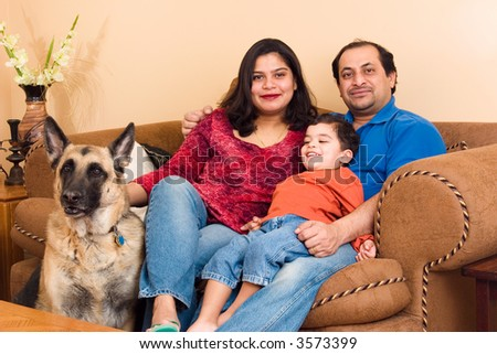 An East-Indian couple site in their living room with their son and dog