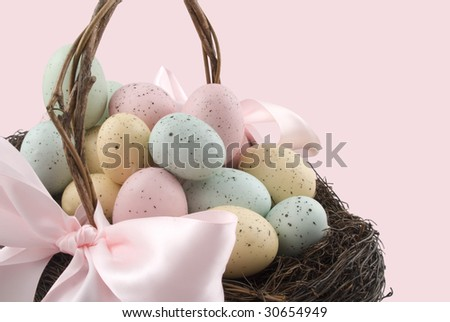 An easter basket with colorful eggs isolated on a pink background - stock photo
