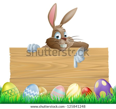 An Easter bunny character peeking over a wooden Easter sign pointing his finger down at space for your message. Surrounded by decorated chocolate Easter eggs