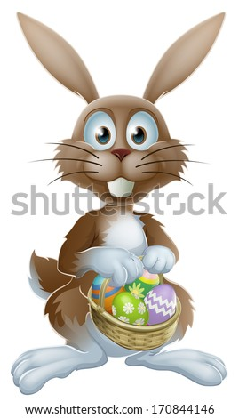 An Easter bunny rabbit holding a basket of decorated painted chocolate Easter eggs - stock photo