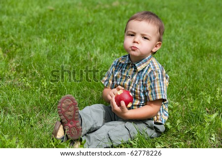 An eating apple little child is sitting on the green grass - stock photo
