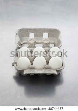 An egg carton with six white eggs on metallic surface. - stock photo