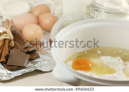 An egg in a pile of flour preparing for baking with kitchen tools - stock photo