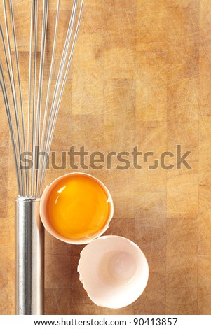 An egg yolk in its shell with a metal whisk on an old wooden chopping board. - stock photo