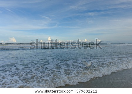 An egret runs for dry land to avoid the incoming tide waves - stock photo