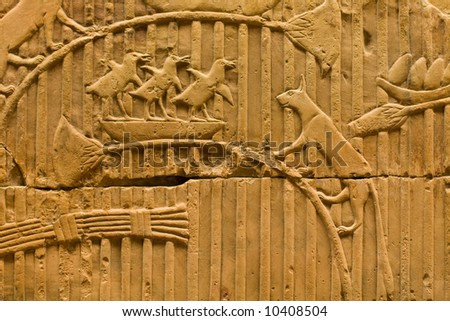 An Egyptian rock carving of a cat about to attack a bird nest - stock photo