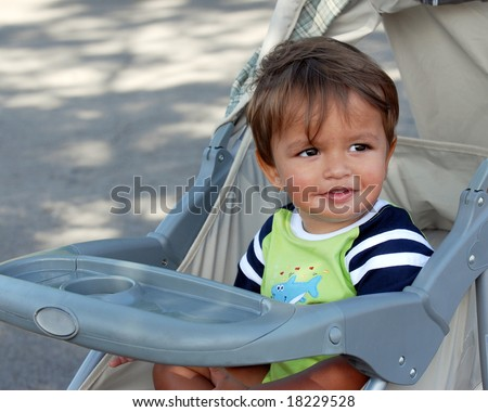An eighteen-month boy enjoying a summertime stroller ride. - stock photo