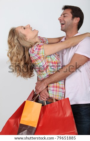 An elated couple embracing after a shopping spree. - stock photo