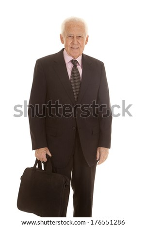 An elderly business man standing holding a bag. - stock photo