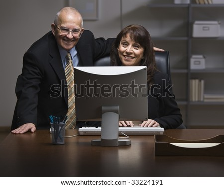 An elderly businessman and a younger businesswoman are working together on a computer in an office.  They are smiling at the camera.  Horizontally framed shot. - stock photo