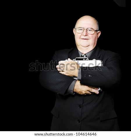 An elderly businessman clutches a silver metal document case tightly to his chest fearful of theft or coporate espionage in a busines safety and security concept - stock photo