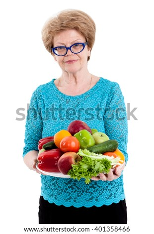 An elderly Caucasian woman carries fruit and vegetable plate, isolated white background - stock photo