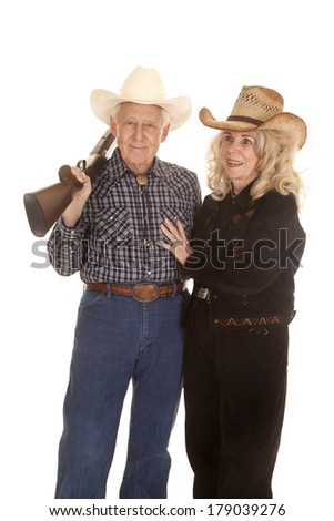 an elderly couple smiling while her cowboy is holding a shot gun over his shoulder.