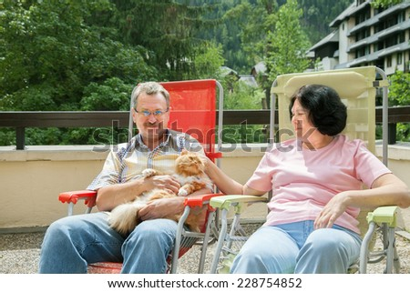 an elderly couple with a cat on the balcony  - stock photo