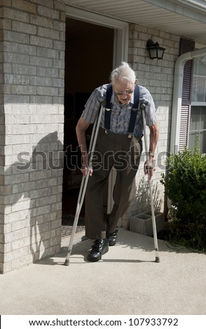 An elderly disabled veteran trying to walk with crutches outside of his apartment on a sunny afternoon.