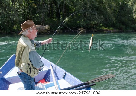 An elderly fisherman reels in a rainbow trout from his drift boat on Oregon's Mckenzie River near Eugene. - stock photo