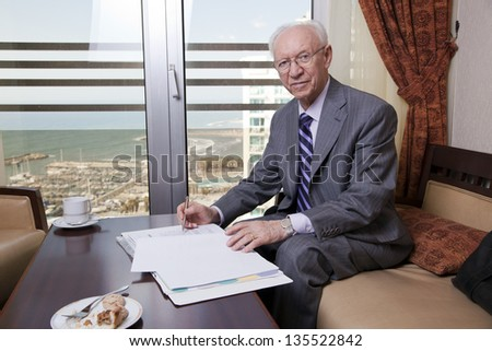 An elderly (in his 80's) business man sitting in a hotel's business lounge, looking at camera with a slight smile on his face, in the middle of going over some papers after having coffee and cake.