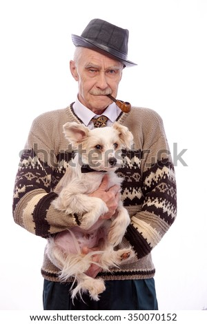 An elderly man holding a small dog.Grandpa smokes a pipe.On his head he is wearing a black hat.A man wearing a sweater. - stock photo