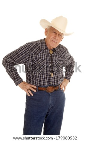 An elderly man in a cowboy hat with his hands on his hips. - stock photo