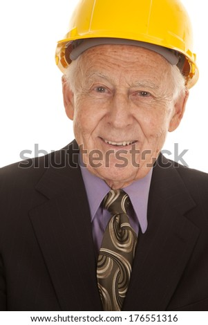 An elderly man in a suit and a hard hat. - stock photo