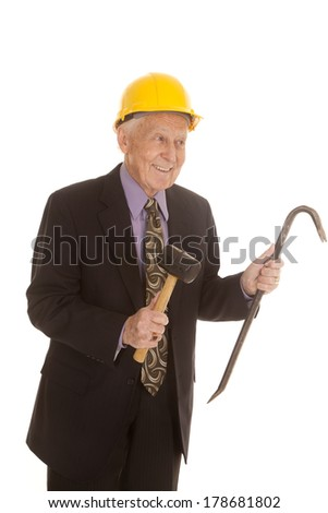 An elderly man in his construction hat and holding on to tools. - stock photo