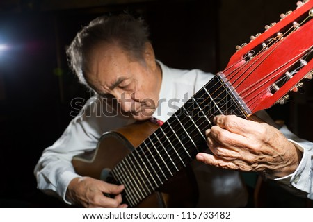 An elderly man in white shirt playing an acoustic guitar. Dark background. Focus on the hand.