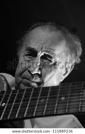An elderly man in white shirt playing an acoustic guitar. Dark background. Monochrome.