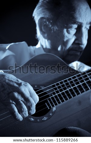 An elderly man in white shirt playing an acoustic guitar. Dark background. Monochrome.  Focus on the hand.