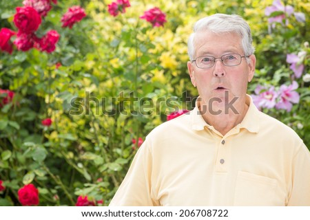 An elderly man is astounded in front of a beautiful rose background - stock photo