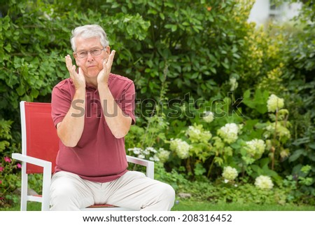 An elderly man is doing a silly face - stock photo