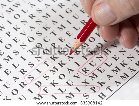 An elderly man is doing crossword puzzle. He has circled a word 'flip' with a red pencil. This puzzle is for finding words in it. The focus point is on the red pen tip. - stock photo