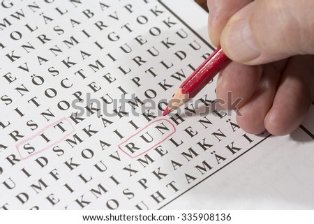 An elderly man is doing crossword puzzle. He has circled a word 'run' with a red pencil. This puzzle is for finding words in it. The focus point is on the red pen tip. - stock photo