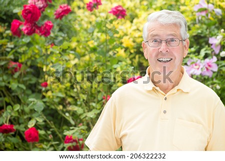 An elderly man is looking expectantly at the camera in front of beautiful rose bushes opening his eyes wide open - stock photo