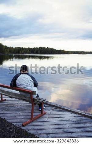 An elderly man is sitting on a bench by the sea and remembering the old times. The man is composed on the left side and he is wearing a cap and a jacket. Image has a vintage effect applied.