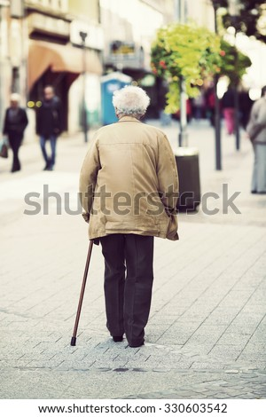 An elderly man is walking in the city with a walking stick. Some unidentified person are walking in the streets. Image has a vintage effect applied. - stock photo